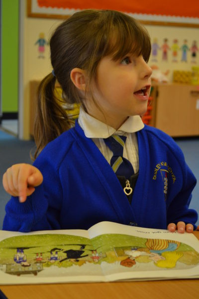 Nuresry girl at Dudley House School pointing to picture in book and excitedly discussing the story