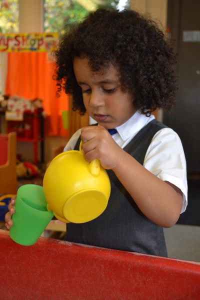 Child pouring sand from a yellow kettle into a cup