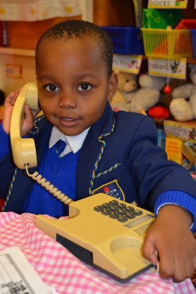 Nursery boy smiling and chattering on the telephone to his friends in the toy shop
