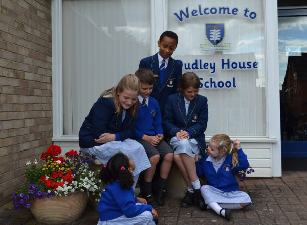 Group of 6 children sat on a bench outside the front of the school