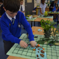 Child adding physical geographical features from plants, Plasticine, rocks etc. on to grid to create a three dimensional map
