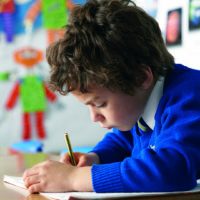 Young boy concentrating hard writing a story