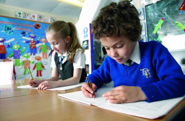 Young boy and girl writing their space adventures after travelling in their class space rocket