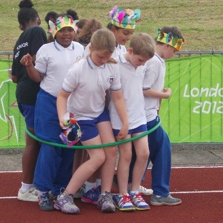 8 children inside a hoop at Mini Olympics problem solving as a team