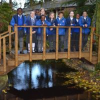 Children standing on a bridge over a pond outside to Holocaust centre at Laxton
