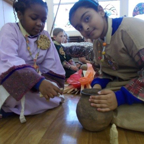 Two girls in Saxon costumes with a clay pot next to a pretend fire