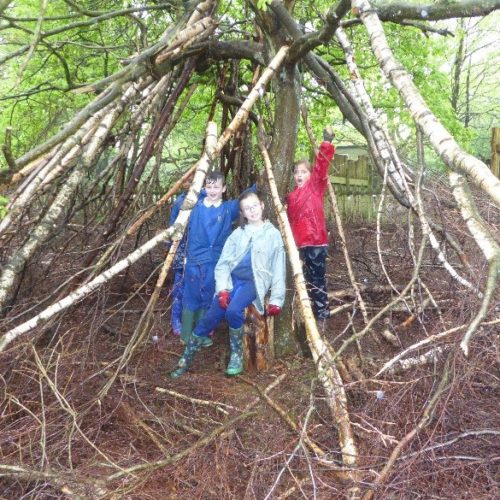 3 wet children standing under a shelter they had made from branckes and sticks in Sherwood Forest