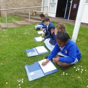 Four children sat on the grass creating geographical field sketches of Dudley Road.